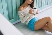 kivágott kilátás nő gazdaság csésze kávé és ül a padlón a konyhában