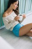 vonzó nő gazdaság csésze kávét, miközben ül a padlón a konyhában