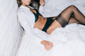 cropped view of young woman in black lingerie and white shirt posing on bed