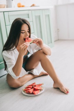 attractive woman in lingerie and white shirt eating watermelon on floor in kitchen