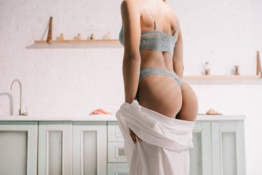 cropped view of sensual young woman posing in blue lingerie and white shirt in kitchen