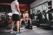 cropped view of personal trainer supervising sportswoman lifting weight in gym