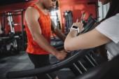 Ausgeschnittene Ansicht eines Trainers, der Fitness-Tracker anschaut, während er neben einem amerikanischen Sportler steht, der auf dem Laufband läuft