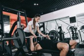pretty, attentive trainer assisting sportsman lifting barbell in gym
