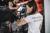 Junge Trainerin schaut Fitness-Tracker an, während stehender Sportler auf Laufband läuft