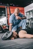 meditato medico africano americano vicino sportivo inconscio ferito con piastra di peso