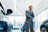 pensive bearded businessman standing near automobiles in car showroom