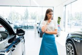young and pensive woman standing near cars in car showroom