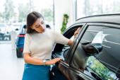 Fotografie atraktivní žena při pohledu na moderní auto v autosalonu