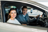 selective focus of pretty woman sitting in car with man