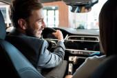 Fotografie selective focus of happy bearded man holding steering wheel near woman in car