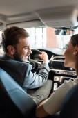 selektivní zaměření šťastný vousatý muž drží volant a při pohledu na ženu v autě