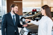 selective focus of woman giving car key to happy bearded man in suit