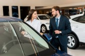 selective focus of cheerful car dealer gesturing while looking at bearded man in car showroom