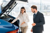 Photo attractive and happy car dealer gesturing near blue car and bearded man