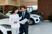 attractive woman standing with bearded man and holding papers in car showroom
