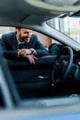 Fotografie selektivní zaměření šťastný vousatý muž při pohledu na moderní auto
