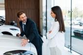 šťastný vousatý prodejce aut gestikulace poblíž atraktivní žena stojící se zkříženými pažemi v autosalonu
