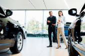 selective focus of man and woman walking in car showroom