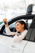 pozitivní mladá žena drží klíček od auta, zatímco sedí v autě