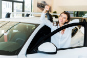 Photo selective focus of positive young woman holding car key