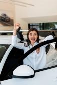 Aufgeregte junge Frau mit Autoschlüssel im Fokus