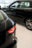 selective focus of black shiny cars in car showroom