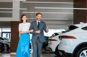 šťastný vousatý muž gestikulace při chůzi se ženou v autosalonu