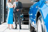 ostříhaný pohled na ženu gestikulující při stání poblíž vousatého muže a auta