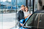 selective focus of beautiful girl gesturing while standing with handsome man and blue car