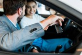 Fotografie selective focus of bearded man holding car key near smiling woman sitting in car