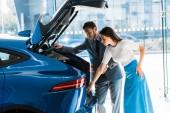 atraktivní žena stojící v blízkosti pohledný vousatý muž a při pohledu na auto kufr