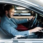 Fotografie selektiver Fokus des gut gelaunten bärtigen Fahrers auf dem Auto sitzend und anrührendes Display