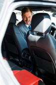 Fotografie selektivní zaměření šťastný muž sedí v moderním autě