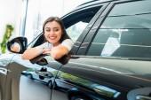 selektivní zaměření veselá žena sedí v lesklém autě