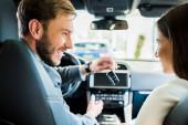 szelektív fókusz boldog férfi és nő néz egymásra autóban