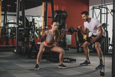 excited trainer shouting while motivating attractive sportswoman lifting barbell