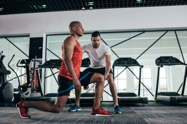 attentive trainer controlling african american sportsman exercising with resistance band