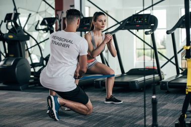 back view of personal trainer controlling attractive sportswoman exercising with resistance band
