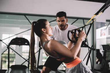cropped view of trainer supporting young sportswoman pulling up on suspension trainer