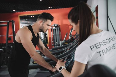 selective focus of personal trainer standing near sportsman running on treadmill