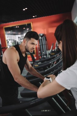 personal trainer looking at fitness tracker while standing near sportsman running on treadmill