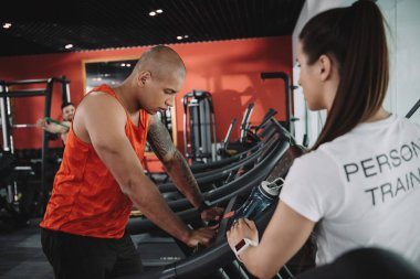 personal trainer in fitness tracker standing near african american sportsman running on treadmill