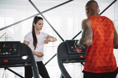 attentive trainer looking at fitness tracker while standing near african american sportsman running on treadmill
