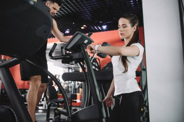 attentive trainer looking at fitness tracker while standing sportsman running on treadmill
