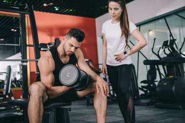 attentive trainer standing near handsome sportsman working out with dumbbell