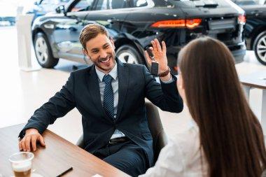 Selective focus of happy bearded car dealer holding car keys near woman stock vector