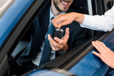 cropped view of car dealer giving car key to bearded man