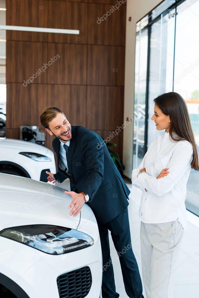 felice barbuto concessionario auto gesturing vicino donna con le braccia incrociate in auto showroom