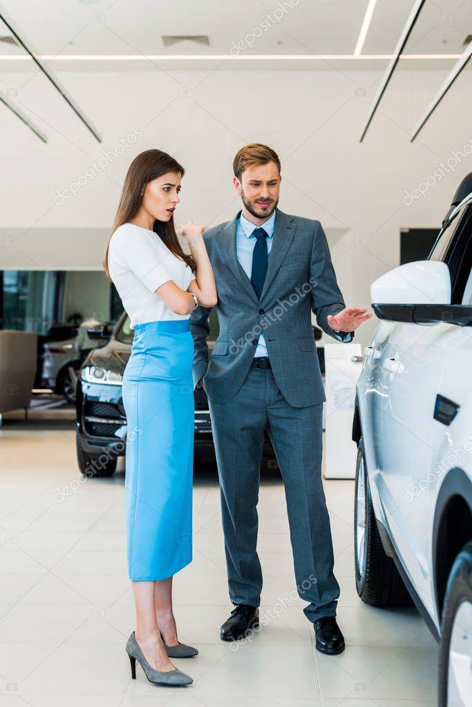 donna sorpresa guardando la macchina e in piedi con l'uomo